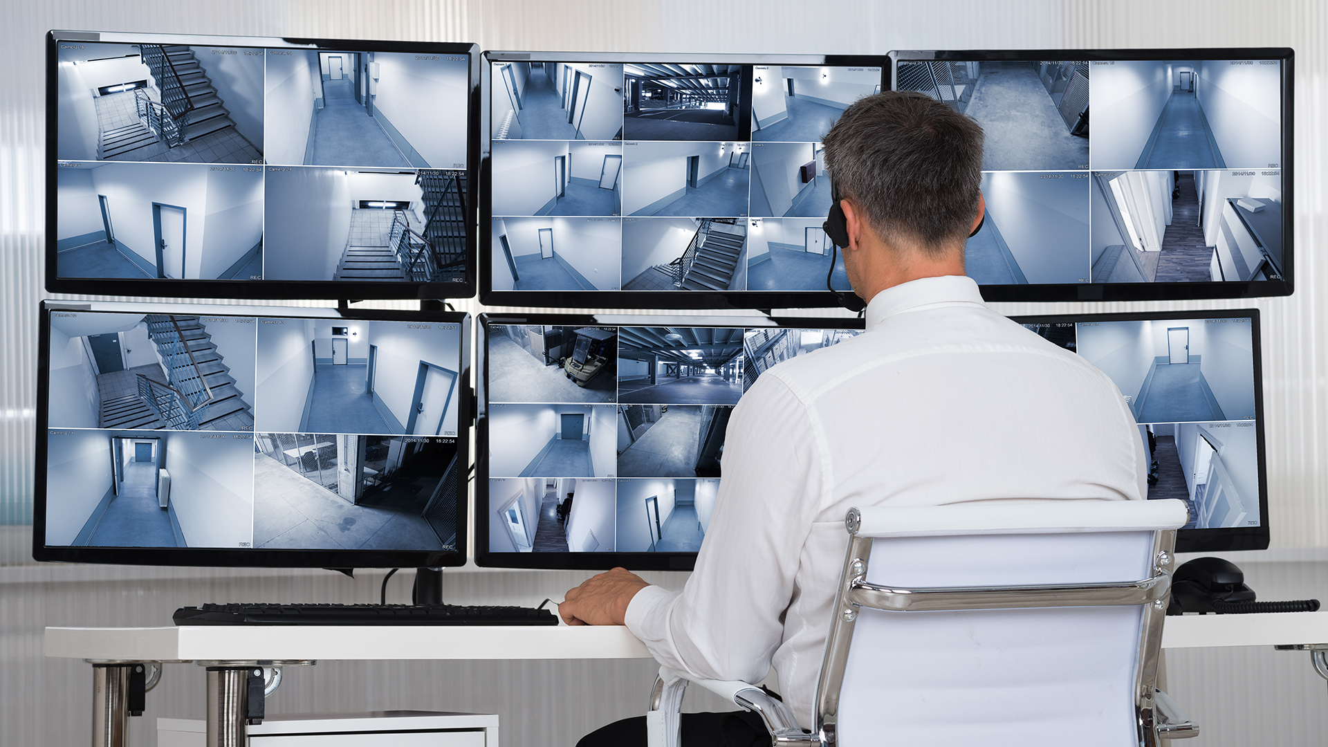 man watching multiple video security feeds